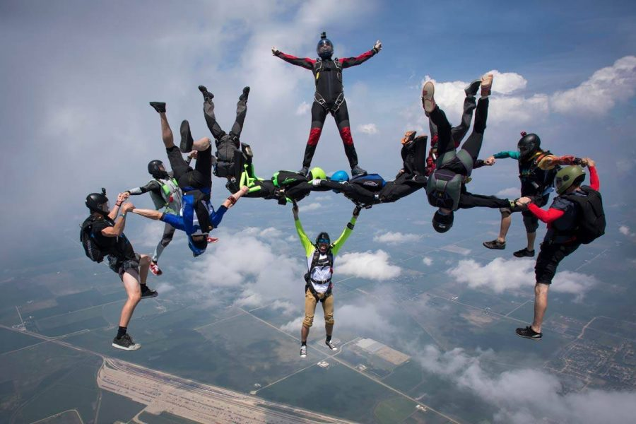 Group of experienced skydivers creating formations during free fall.