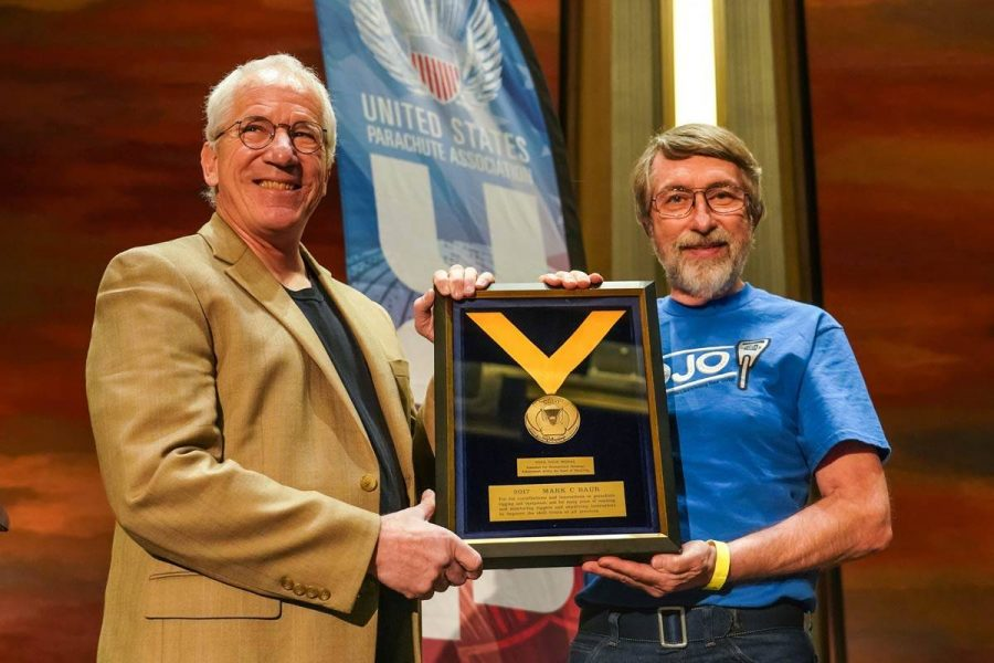 Two gentlemen holding an award at the PIA Symposium.