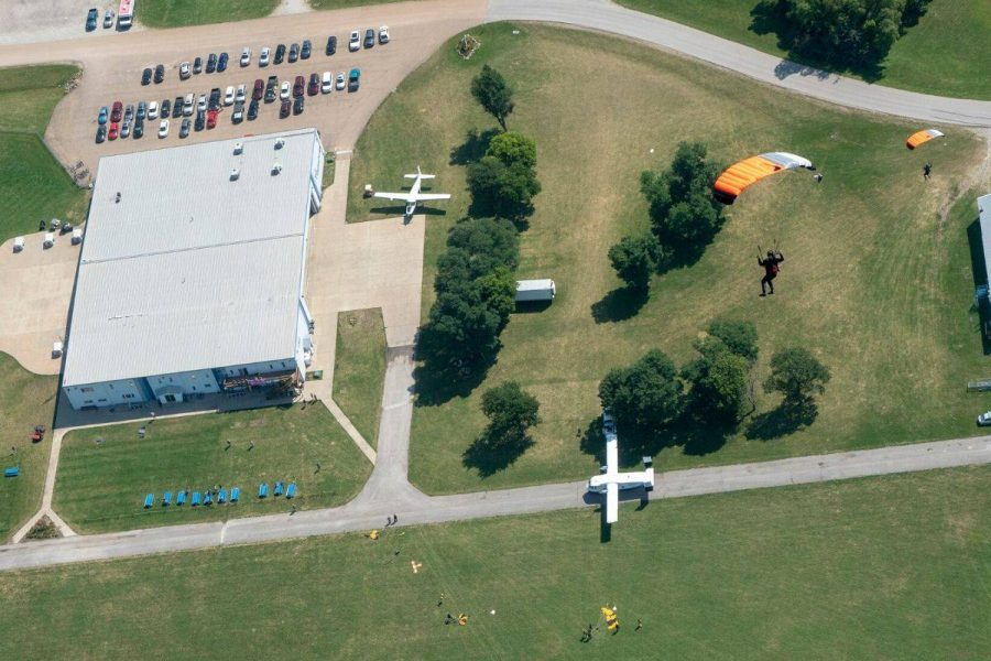 Aerial shot of drop zone with skydivers making landing.