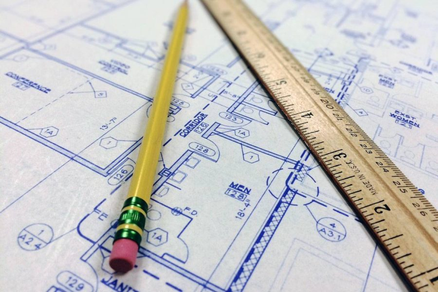 Pencil and ruler laying on top of blue prints.