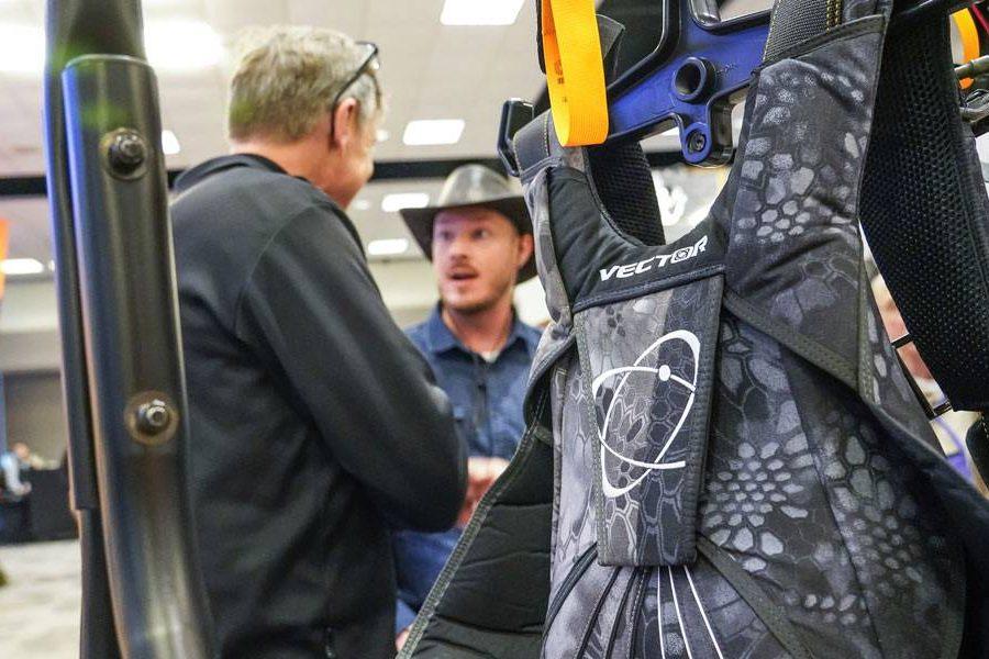 two men talk at PIA symposium behind vector skydiving rig