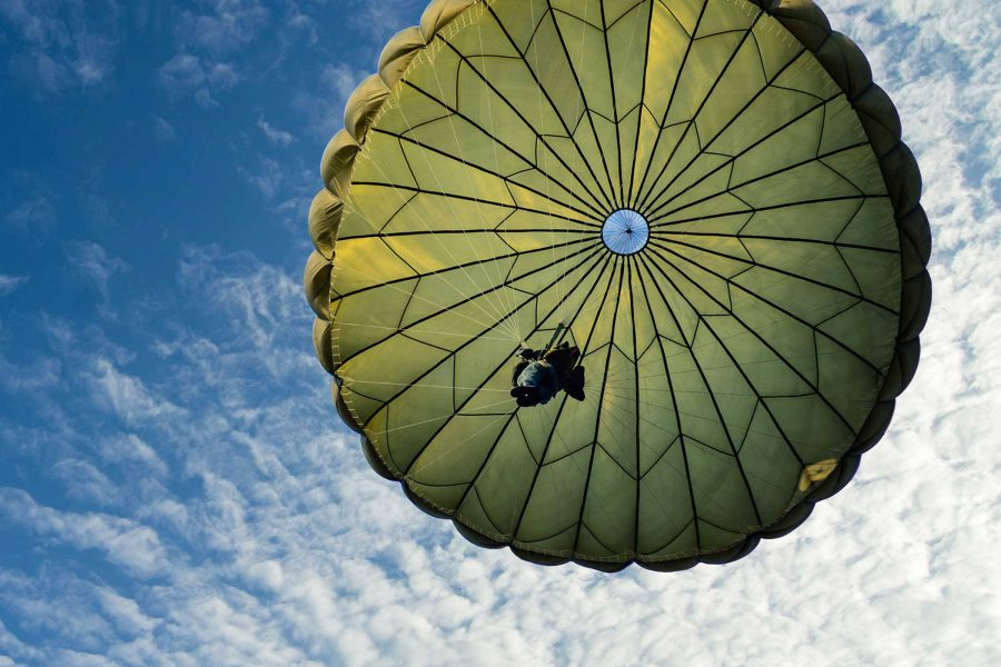 Skydiver nearing his landing with green canopy.