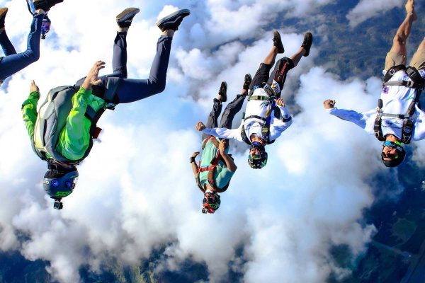 Group of experienced jumpers in free fall with white clouds below them.